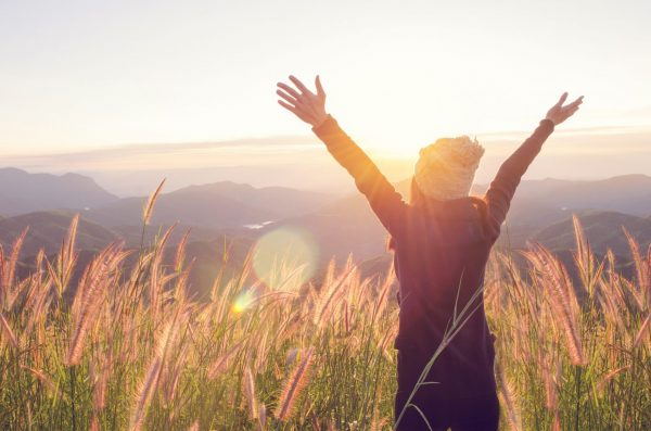 Happy person in field at sunrise