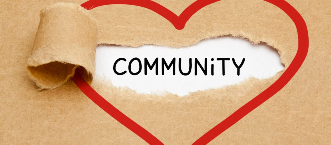 Handwritten word Community appearing behind torn red heart on brown paper.