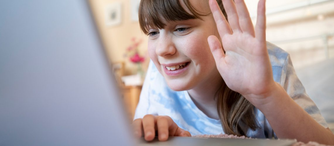 Smiling Girl In Bedroom Talking With Friends On Social Media Using Laptop Computer