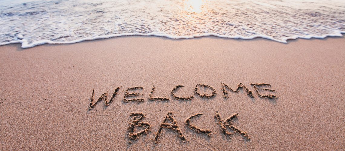welcome back, text on sand beach, tourism concept